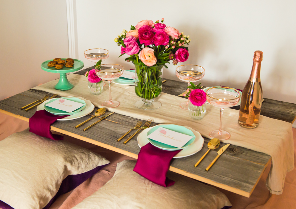 A springtime, picnic style table setting with a mixture of subdued pastels and bright flowers