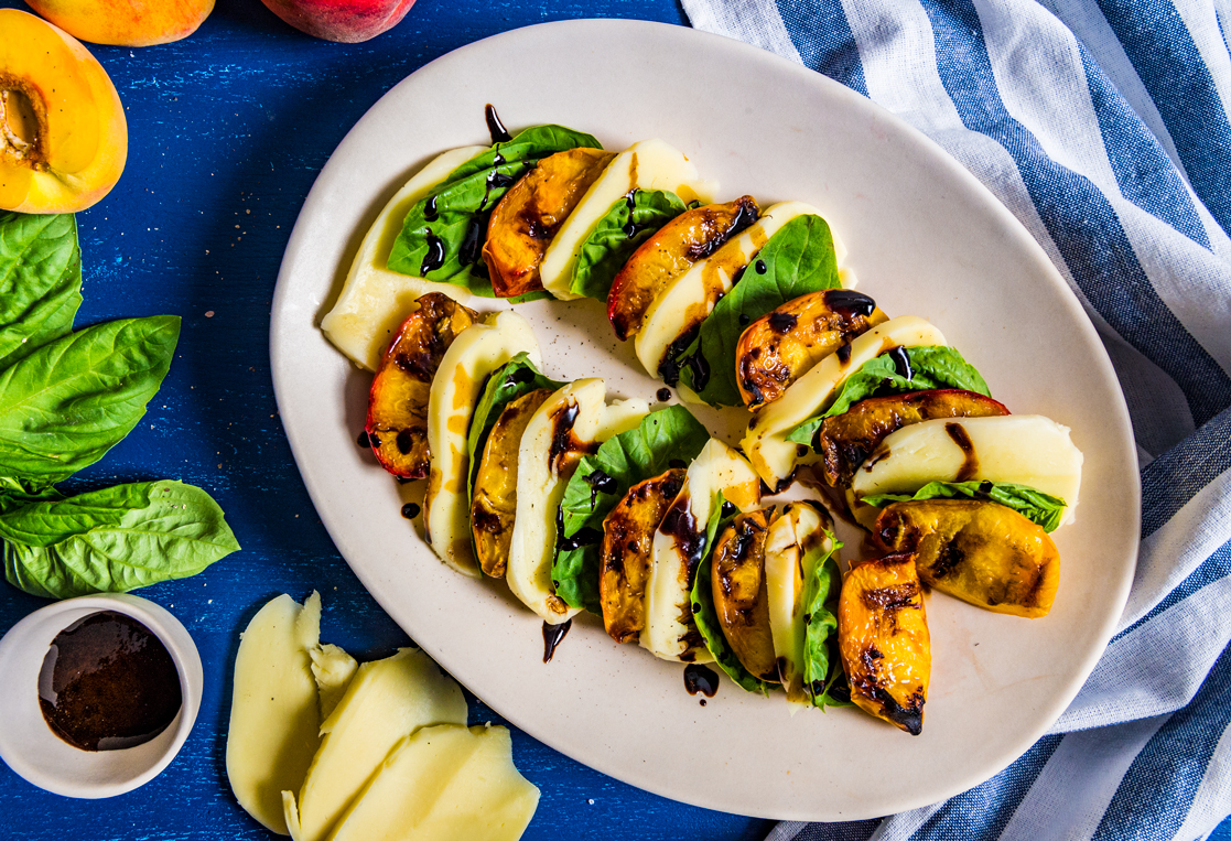Sweet grilled peaches rested on top of sliced mozzarella, fresh basil and topped with balsamic drizzle