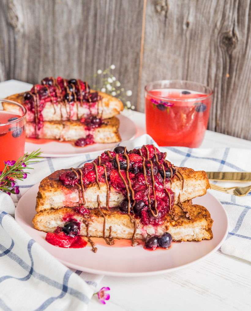 Whipped cream cheese and bananas stuffed between 2 french toasts and topped with a fresh berry coulis