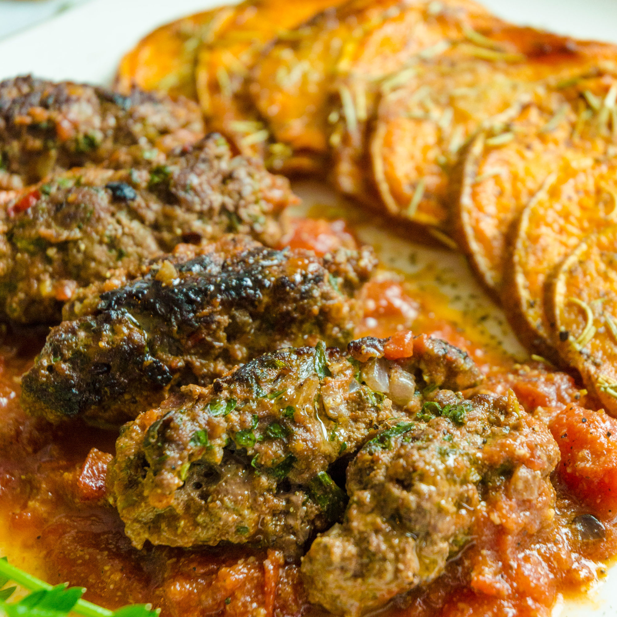 Middle Eastern spices mixed with fresh herbs rolled into minced meat and baked in a spiced tomato sauce
